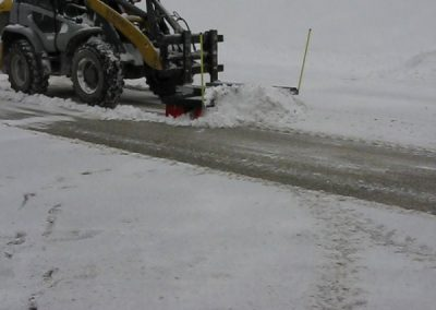 Su šepečiu nuvalysite sniegą keliuose
